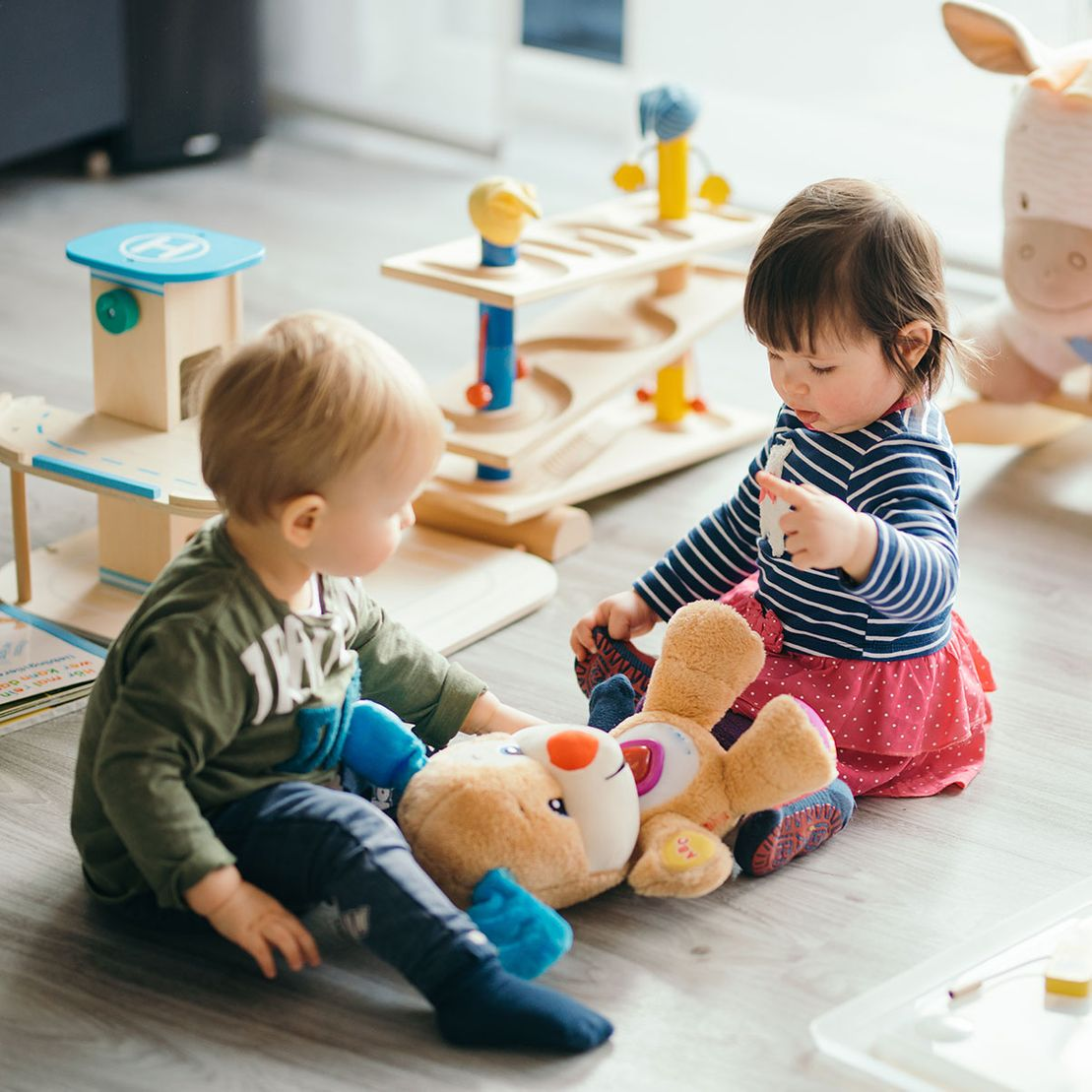 little girl and boy playing with toys